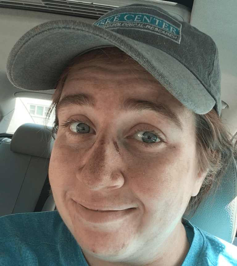 Image of Liz sitting in her car after working in the field, with dirt smudges on her face