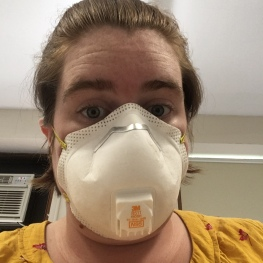 Image of Liz in a protective mask, while doing work in a lab.
