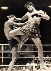 Image of two men fighting, in the Muay Thai style. The man on the right is Samart Payakaroon, a Muay Thai and Boxing world champion.
