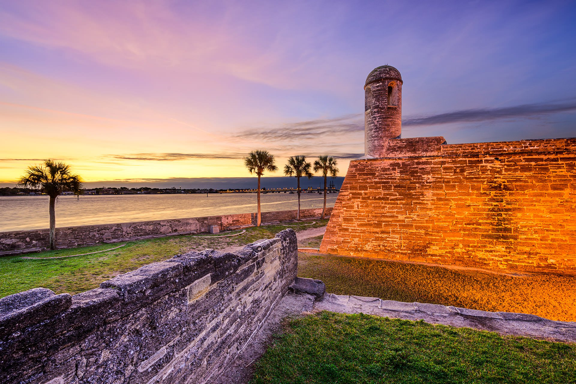 Image of the outside of the Castillo de San Marcos National Monument's eastern wall at sunset, showing the St. Augustine harbor.