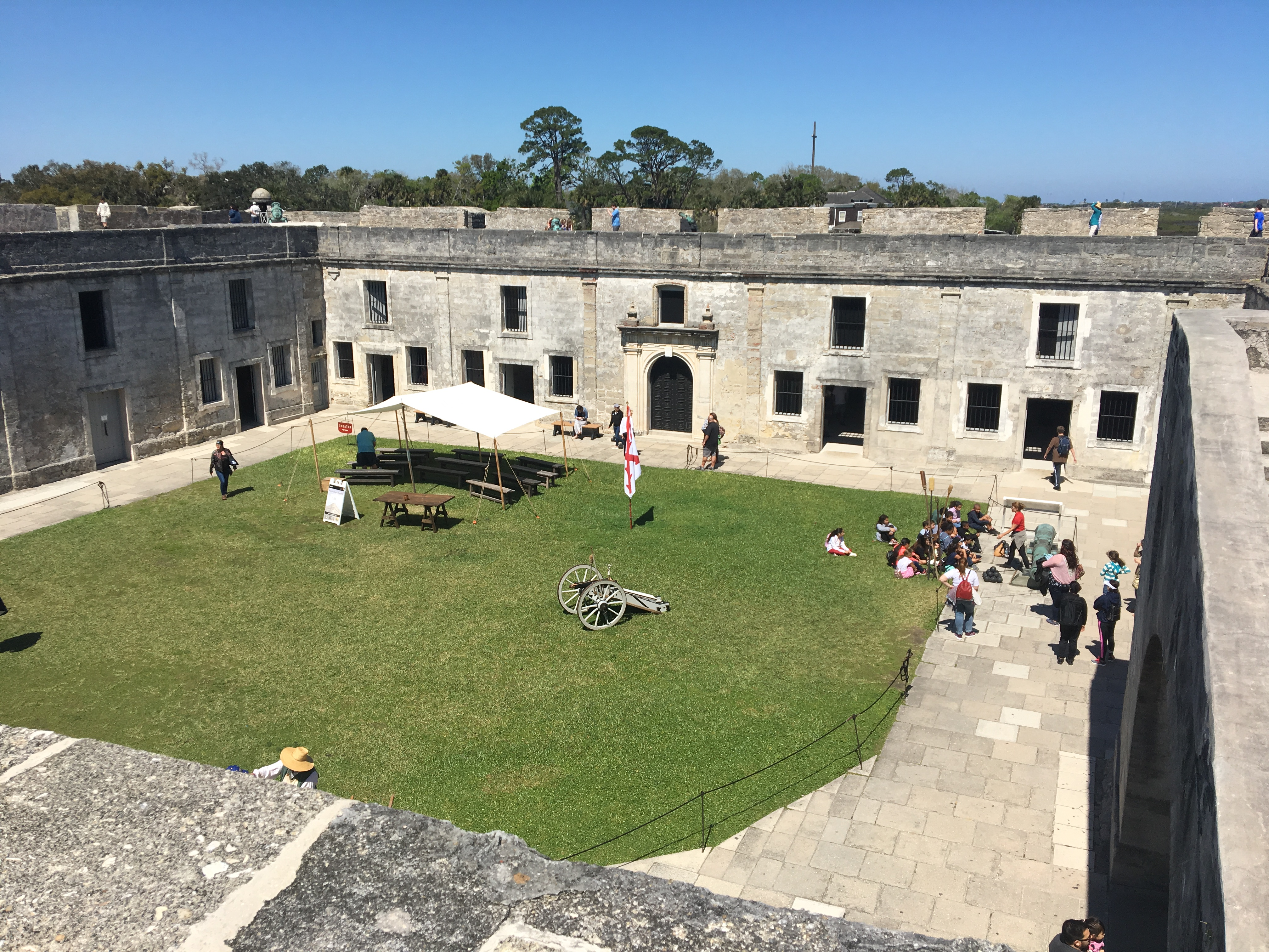 Image of inner courtyard of the Castillo de San Marcos National Monument, showing a green grass area, a cannon demonstration, and a tent where public interpretation occurs.
