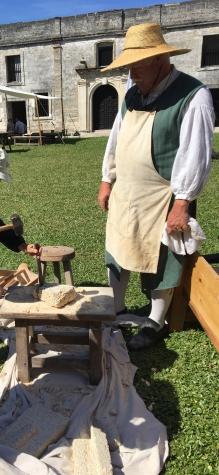 Image of a man wearing historical clothing, demonstrating the making of coquina bricks.