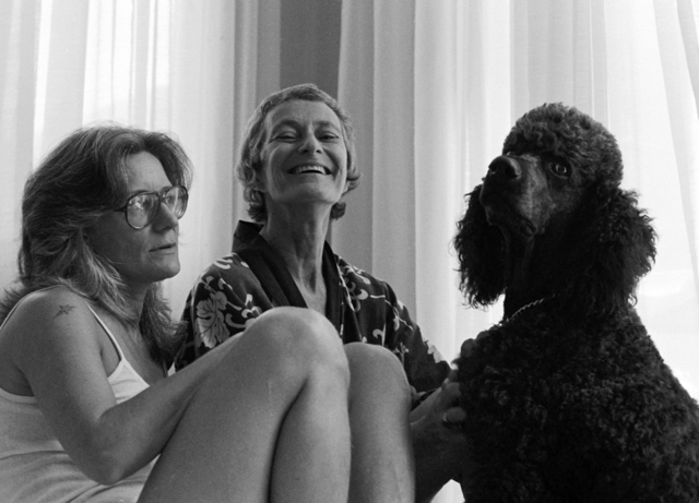 Image of two women, Sally BInford (center) and her partner Jan, and a black standard poodle, Jake. Sally is laughing and looking into the camera, Jake is looking toward the camera, and Jan looks off to the side.