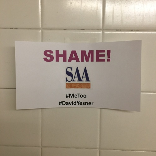 "Sign stating the following: ""SHAME! SAA (logo) #MeToo #DavidYesner"""