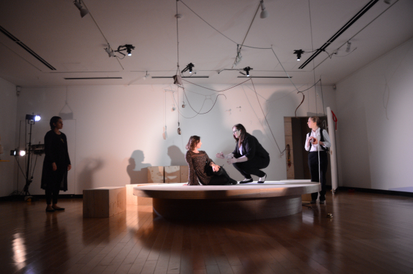 Image showing four women in a play. One is standing in shadow on the left, watching the others, two are on top of a circular table, one sitting down and one crouching. The fourth woman is on the far right, watching the two women on the table. The room is stark white, with wooden blocks scattered about, and strange objects hanging from the ceiling.