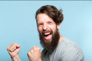 """Stockphoto of a bearded man with his two fists balled up and a thrilled expression on his face. Might be saying """"YAH!""""."""